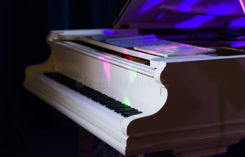 Biały uroczysty pianino iluminujący barwionymi światło reflektorów fotografia royalty free
