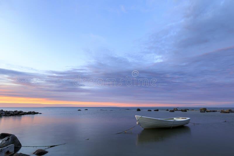 Biała łódź w morzu przy zmierzchem fotografia stock