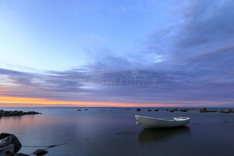 Biała łódź w morzu przy zmierzchem obrazy royalty free