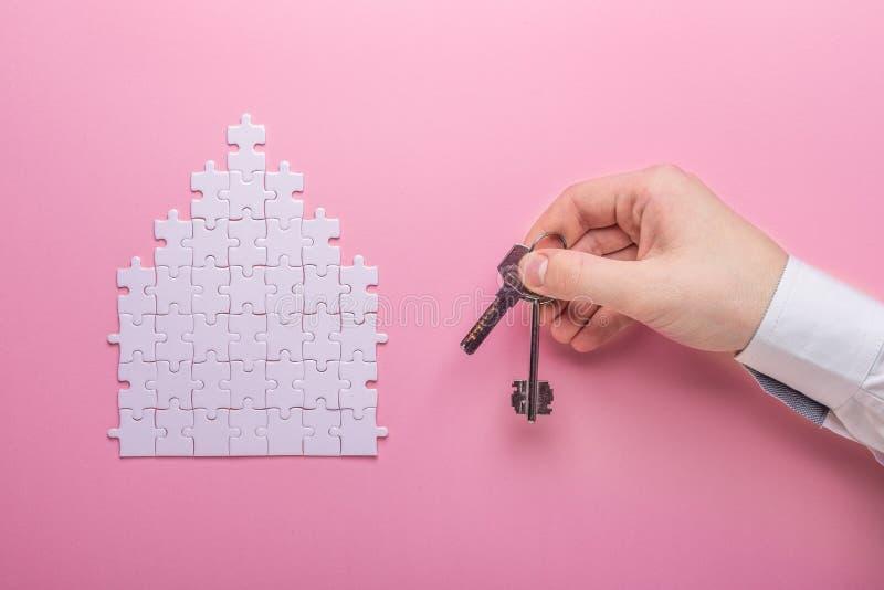 Biała łamigłówka Domowa kształt łamigłówka Pojęcie czynsz, hipoteka - ręka trzymająca odizolowane white Różowy tło Odgórny widok zdjęcie royalty free