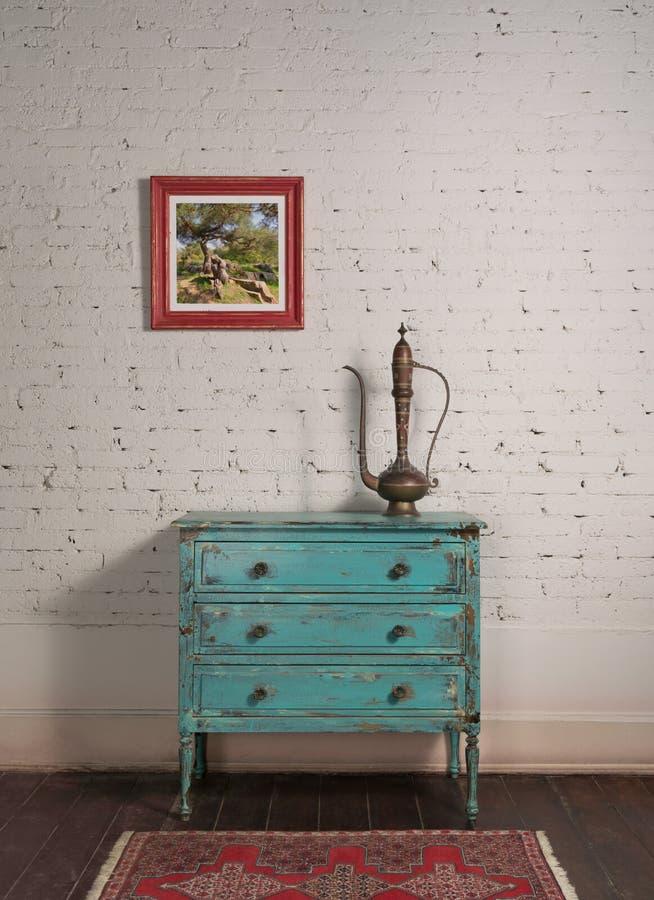 Biała ściana z cegły i antykowy miedziany dzbanek na szafce z turkusami i wiszącym malowaniem zdjęcie stock
