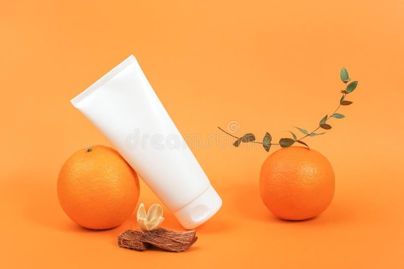 Biała, ślepa butelka kosmetyczna, tubka z kremem, płyn do ciała, twarzy lub dłoni, pomarańczowe owoce i zielona gałązka eukalipt  zdjęcie stock