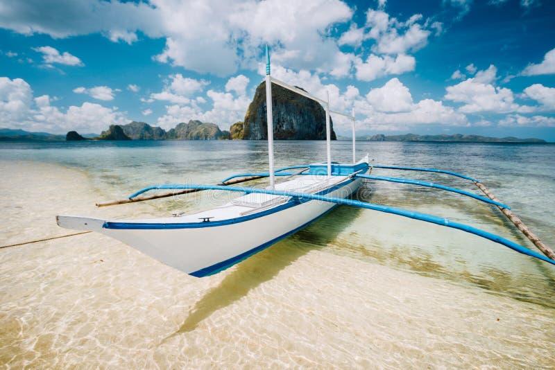Biała banca łódź na piaskowatej plaży gotowej dla wyspy chmielenia wycieczki Zadziwiać Pinagbuyutan wyspę w tle pi?kne zdjęcia stock