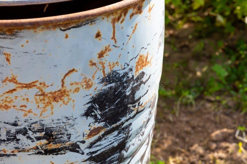 Biała beczka z żeliwa wyłuszczona z pomalowanej zardzewiałej farby, posypana czarnymi plamami, w stylu chrząszcza fotografia stock