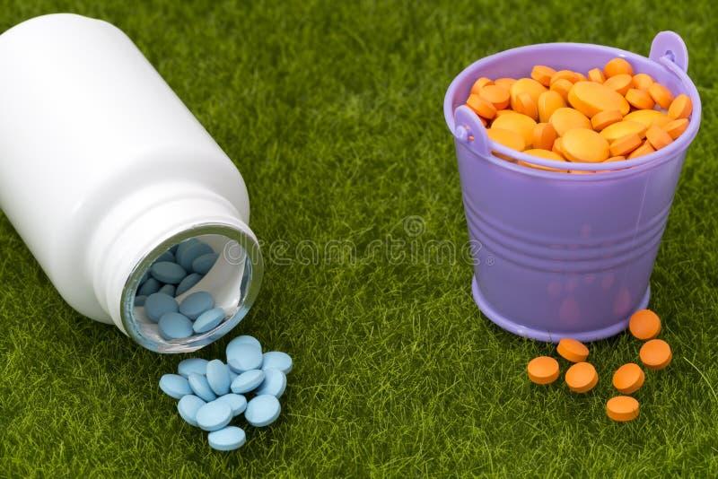 Biała butelka błękitni wiadra i pigułki wypełniał z pomarańczowymi pastylkami obrazy stock