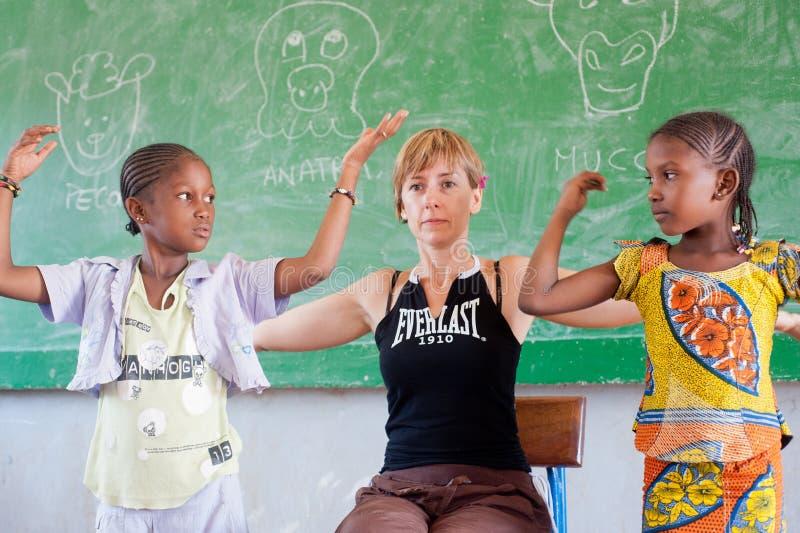 Biała caucasian kobieta uczy czarnych dzieci w Afryka zdjęcia stock