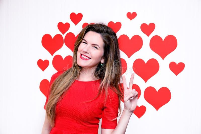 Biała caucasian kobieta z czerwonymi wargami daje odliczającej ręce na kierowym kształtnym tle (dwa znak) Walentynki ` s zdjęcie stock