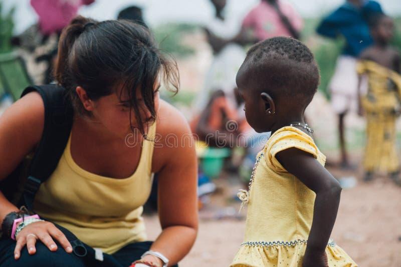 Biała caucasian młoda kobieta bawić się z czarnych afrykanów ludźmi w wiosce zdjęcia royalty free