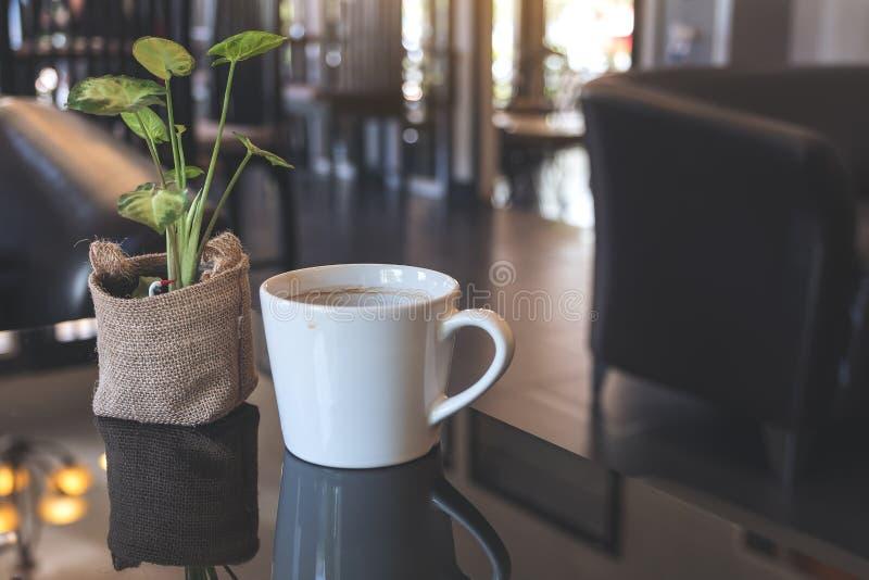 Biała ceramics filiżanka gorąca kawa i mały drzewny garnek na stole w kawiarni obrazy stock
