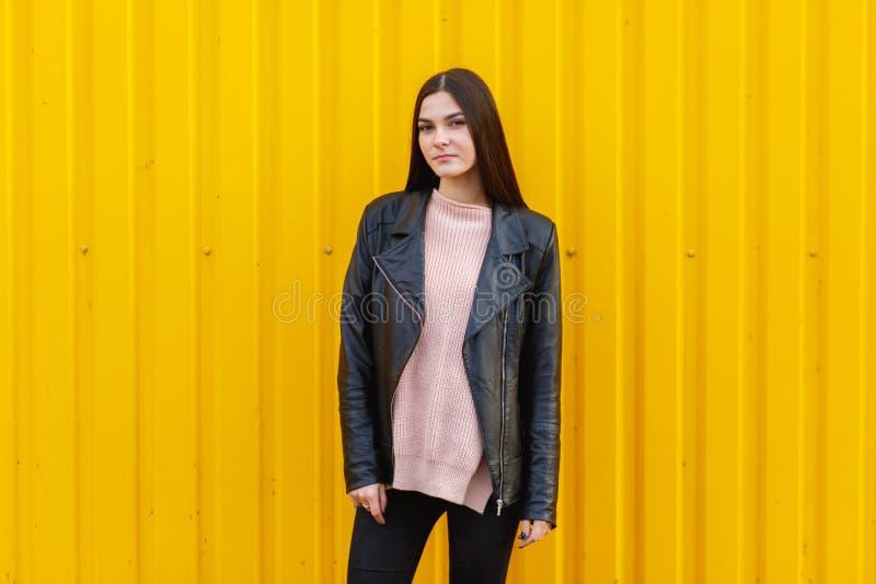 Biała dziewczyna w czarny kurtki pozować plenerowy z kolor żółty ścianą blisko obrazy stock