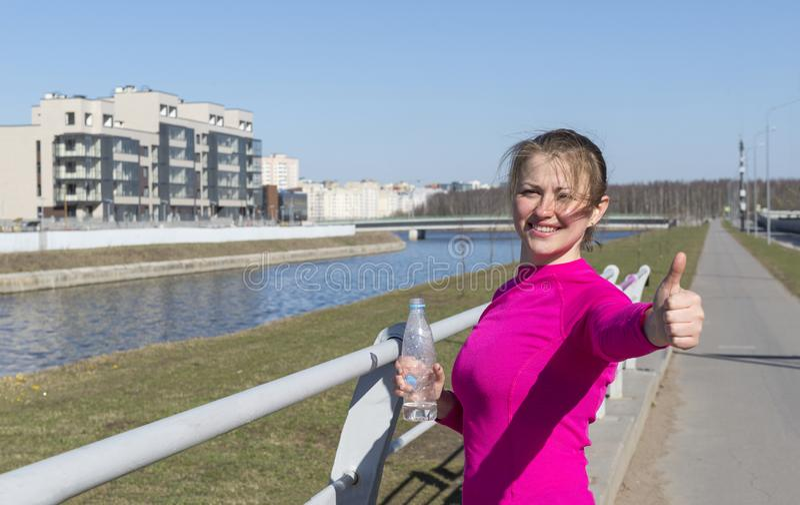 1 biała dziewczyna w różowym sporta wierzchołku z butelką woda jej ręk przedstawień znaka klasa, młoda kobieta outdoors n zdjęcie royalty free
