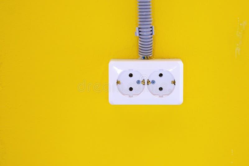 Biała elektryczna nasadka na żółtej ścianie E kosmos kopii zdjęcie stock