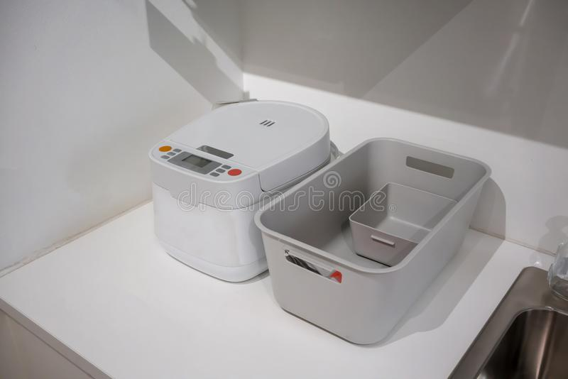 Biała elektryczna ryżowa kuchenka i popielaty plastikowy kosz na kuchni si obrazy royalty free
