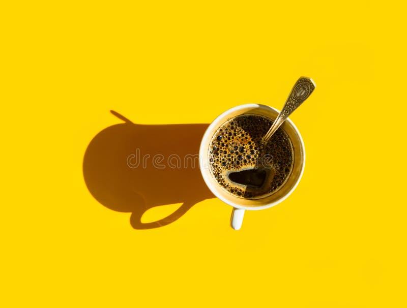 Biała filiżanka świeżo warząca kawa z foamy crema herbacianą łyżką na stałym żółtym tle Odgórny widok Ranku śniadania energia obraz stock