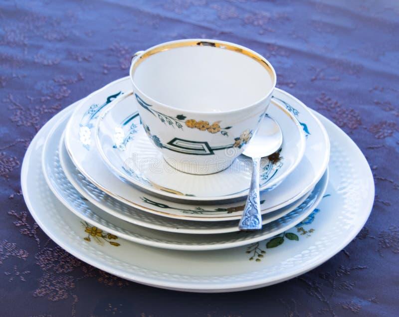 Biała filiżanka dla herbaty, pięć talerzy i łyżki, zdjęcie stock