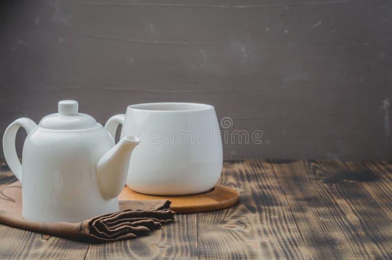 biała filiżanka herbata i teapot na czarnym drewnianym tle, selekcyjnej ostrości i copyspace, obrazy stock