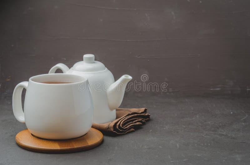 biała filiżanka herbata i teapot na czarnym kamiennym tle, copyspace i selekcyjnej ostrości, fotografia stock