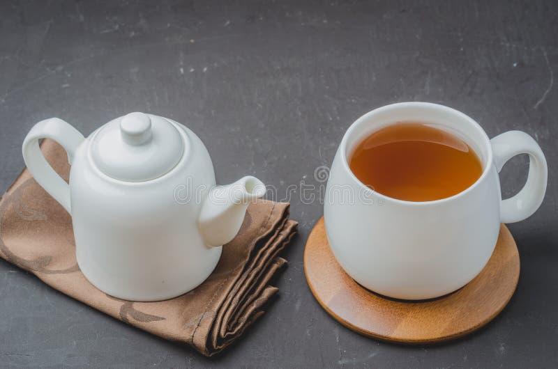 biała filiżanka herbata i teapot na czarnym kamiennym tle, odgórny widok zdjęcie stock