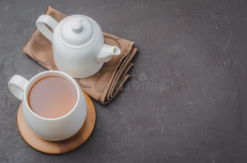 biała filiżanka herbata i teapot na czarnym kamiennym tle, odgórnym widoku i copyspace, obraz royalty free