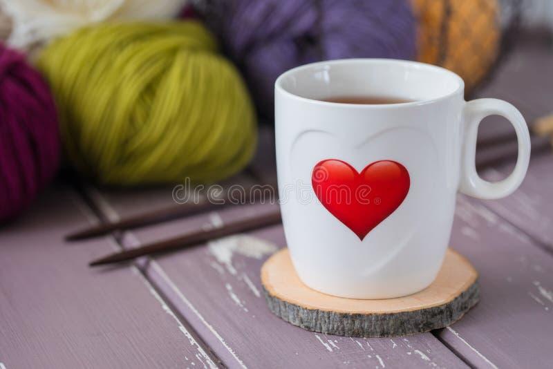 Biała filiżanka herbata z czerwonym drukowanym sercem na tle kolorowa przędza i dziewiarskie igły zdjęcie royalty free