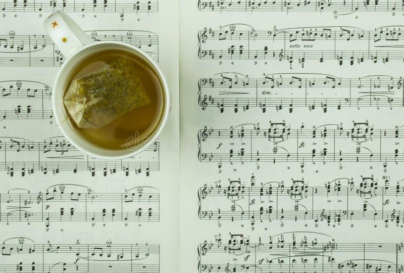 Biała filiżanka herbata z herbacianą torbą i muzyczne notatki ciąć na arkusze jako tło obraz stock