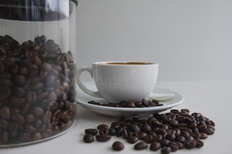 Biała filiżanka i kawowe fasole w szklanej butelce obraz royalty free