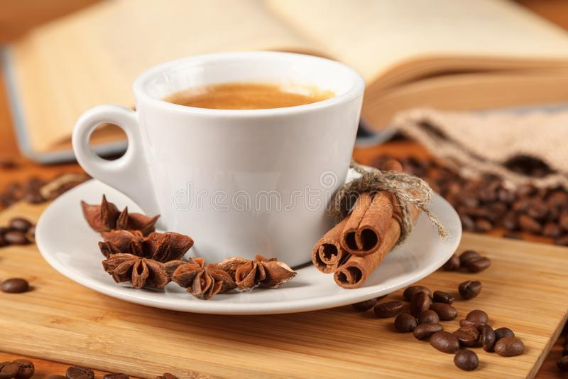 Biała filiżanka kawy kawa espresso otaczająca obok piec kawowe fasole, cynamon, anyż i otwarta książka na drewnianym stole, fotografia stock