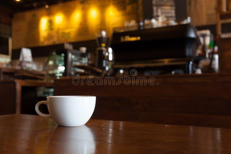Biała filiżanka kawy na drewnianym barze w sklep z kawą plamy tle zdjęcie royalty free