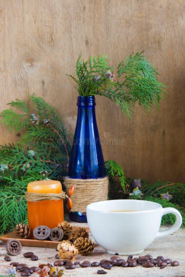 Biała filiżanka kawy, piec kawowe fasole, świeczka, błękitny szkło bo obraz royalty free