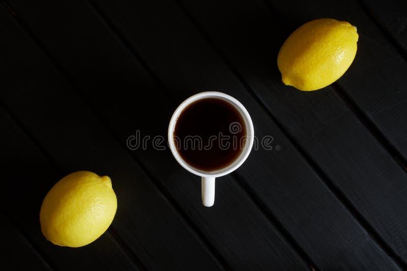 Biała filiżanka z czarną herbatą i dwa żółtymi cytrynami na ciemnym drewnianym stole na widok minimalista obraz royalty free