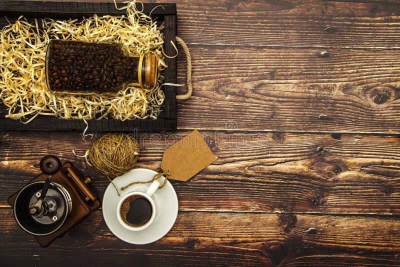 Biała filiżanka z czarną kawą i kawą groszkuje na drewnianym stołowym tle na widok miejsce tekst zdjęcie stock