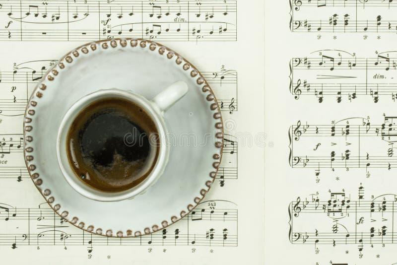 Biała filiżanka z czarną kawą i stronami z klasycznymi muzycznymi notatkami jako tło jako czas dla pojęcia kawowego i muzycznego obrazy stock