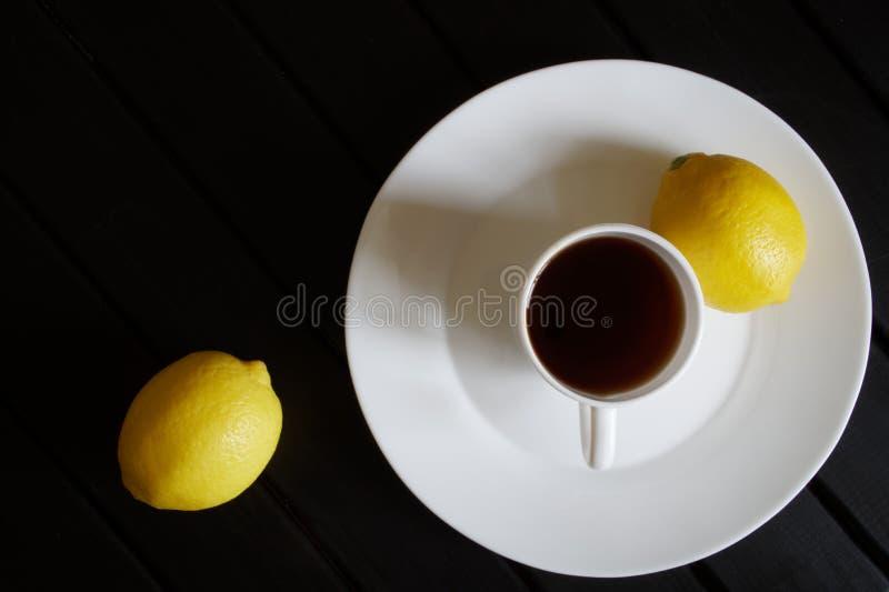 Biała filiżanka z czarnej herbaty stojakami w spodeczku na ciemnym drewnianym stole W pobliżu są dwa żółtej cytryny na widok mini zdjęcie royalty free