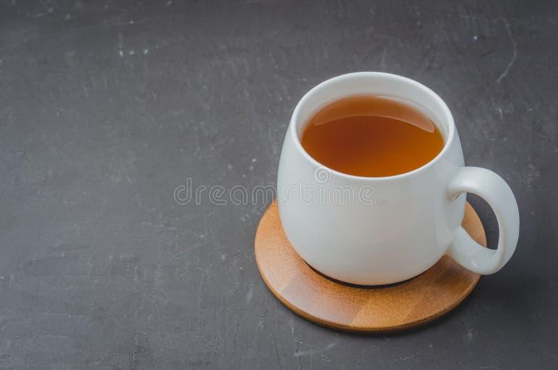 biała filiżanka z herbatą na bambusowym poparciu na czarnym kamienia stole, copyspace zdjęcia royalty free