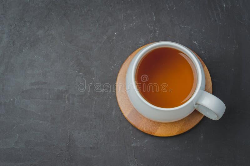 biała filiżanka z herbatą na bambusowym poparciu na czarnym kamienia stole, odgórny widok, copyspace zdjęcie stock