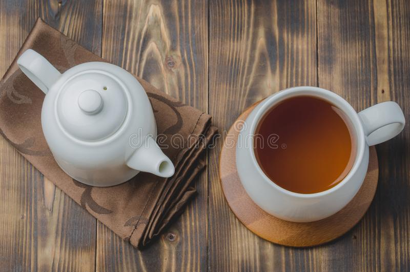 biała filiżanka z herbatą na bambusowym poparciu i teapot na pielusze na drewnianym stole, odgórny widok obraz royalty free