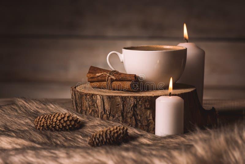 Biała filiżanka z kawą, świeczkami, cynamonem, futerkiem i rożkami, fotografia stock