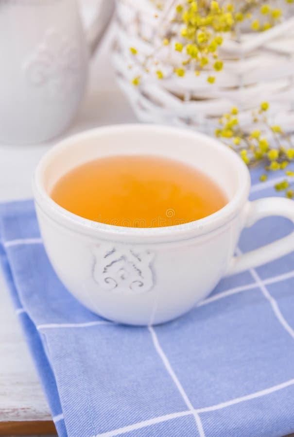 Biała filiżanka z ziołową herbatą na błękitnej pielusze, łozinowy kosz z kwiatami, miotacz, biały stołowy wierzchołek zdjęcia stock