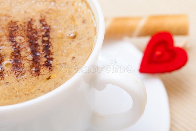 Biała filiżanki coffe gofra rolka z kremowym sercem. Miłości valentine dzień zdjęcia stock