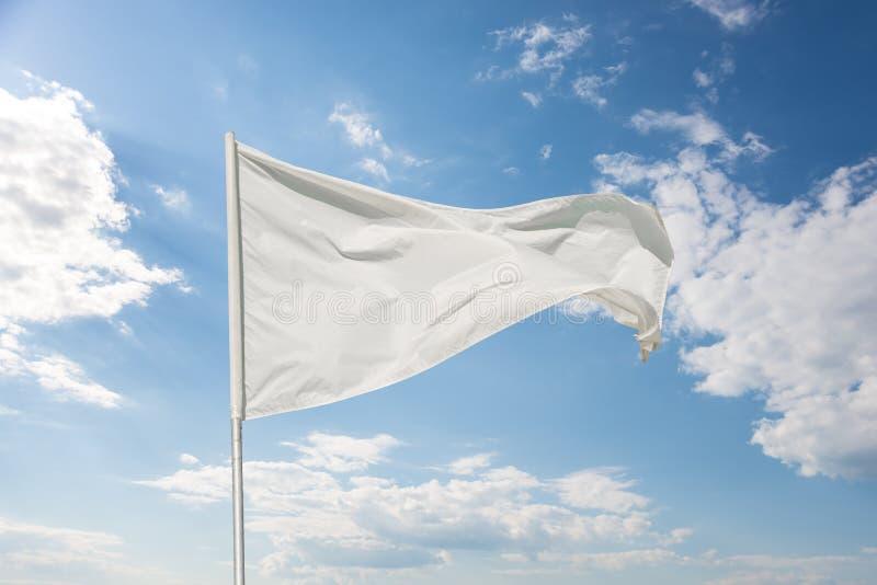Biała flaga przeciw niebieskiemu niebu obraz stock