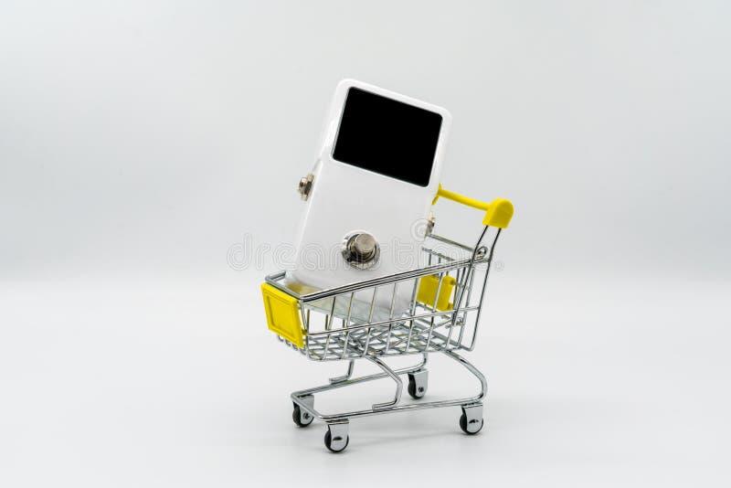 Biała gitara pedałowa i żółty wózek na zakupy odizolowywający na bielu zdjęcie stock