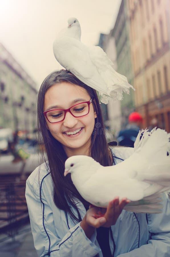 Biała gołąbka siedzi na głowie roześmiana dziewczyna Rozrywka dla turystów w St Petersburg obraz stock