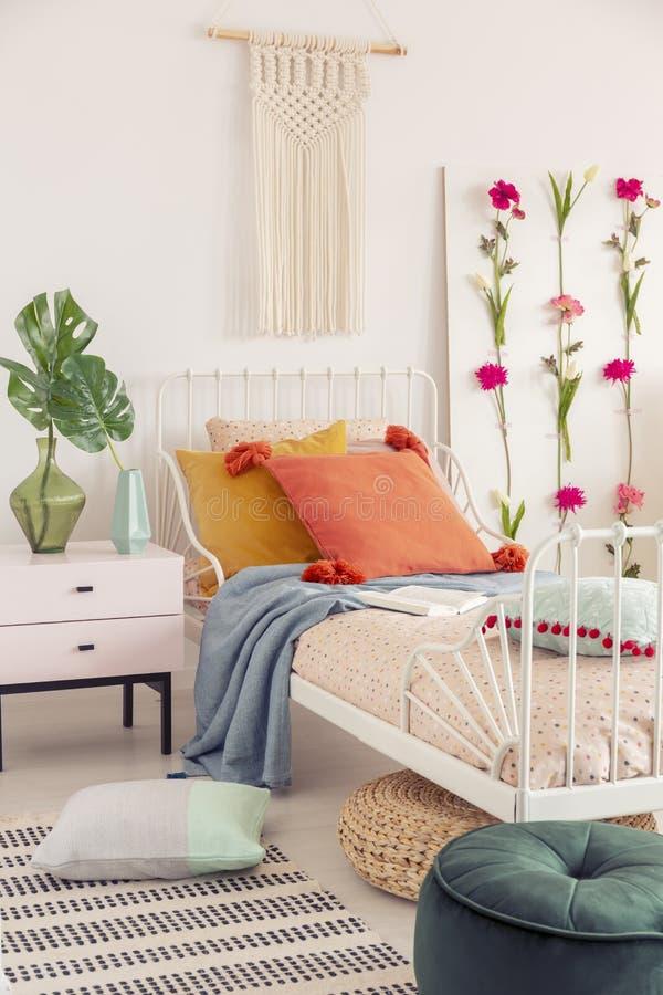 Biała handmade makrama nad nad pojedynczy metalu łóżko z kolorowymi poduszkami i wzorzystym duvet, istna fotografia fotografia stock