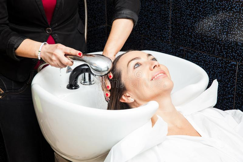 Biała kobieta dostaje włosianego obmycie w piękno salonie fotografia royalty free