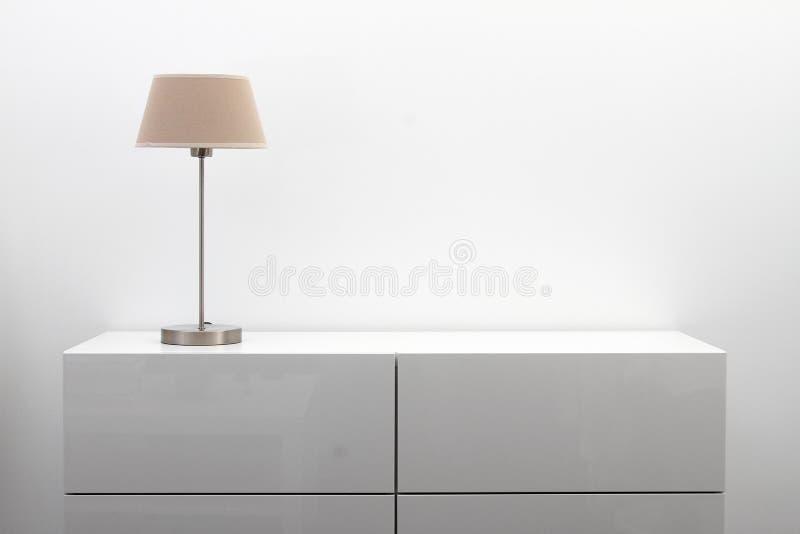 Biała komódka z stołową lampą w jaskrawym minimalizmu wnętrzu zdjęcia royalty free