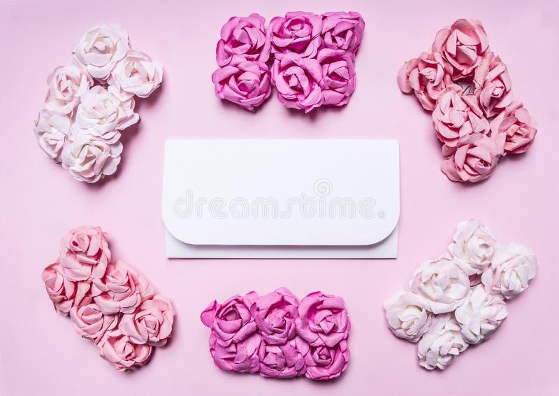 Biała koperta na różowym tle z kafelkowym wokoło plików stubarwnego róża odgórnego widoku zakończenia miejsca up tekst, rama obraz royalty free