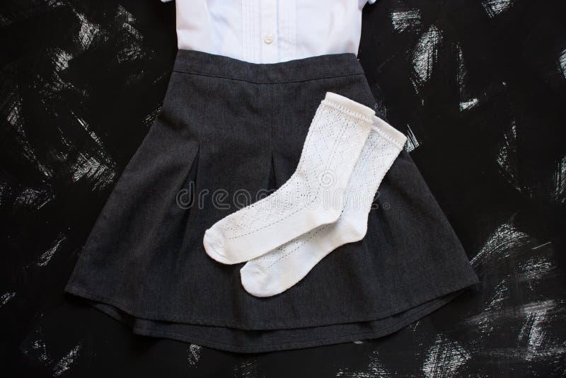 Biała koszula, siwieje spódnicy i materiały dostawy na czarnym tle Pierwszy Wrzesień, nowy rok szkolny obrazy stock