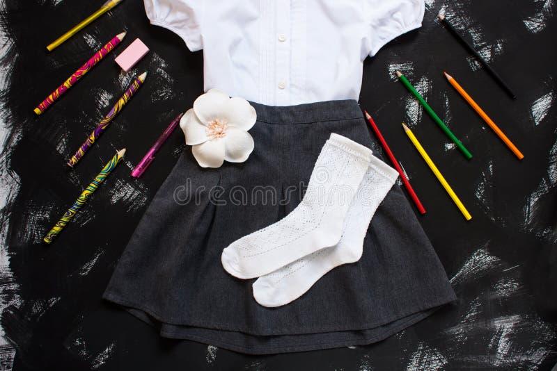 Biała koszula, siwieje spódnicy i materiały dostawy na czarnym tle Pierwszy Wrzesień, nowy rok szkolny zdjęcia stock