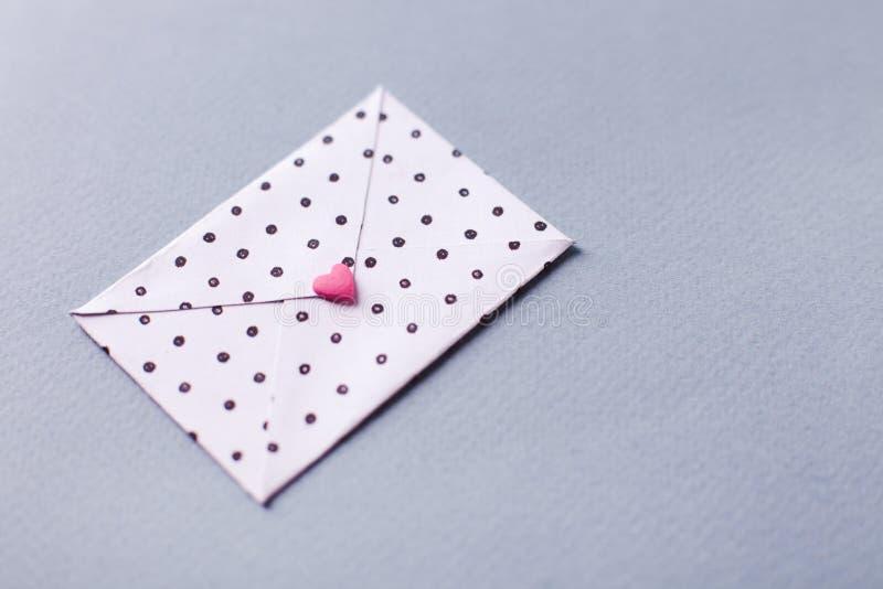 Biała kropkowana koperta z różowym sercem kształtował postać Wręcza wykonującego ręcznie list miłosnego dla Świątobliwego walenty fotografia stock