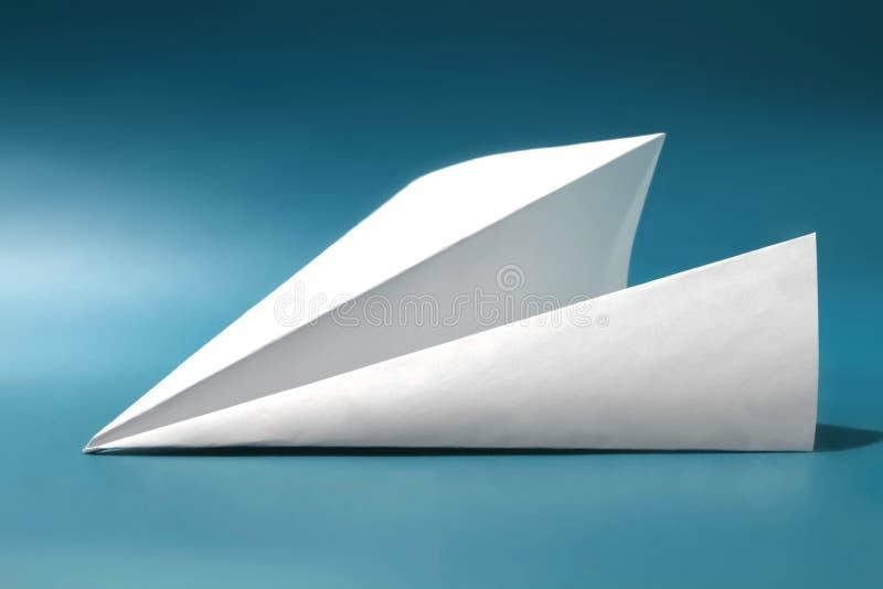 Biała księga samolot na zmroku - błękitny koloru tło zdjęcia royalty free